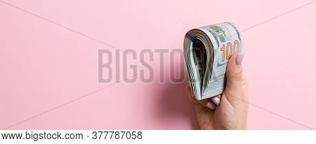 Female Hand Holding Tightly A Bundle Of Money. Top View Of One Hundred Dollars On Colorful Backgroun