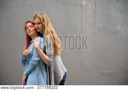 Two Happy Girlfriends Are Hugging On The Background Of A Gray Wall. Gentle Hugs Of A Female Lesbian