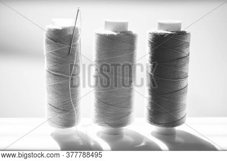 Three Spools Of Thread And A Needle On A White Bright Table. Bw Photo, Side View
