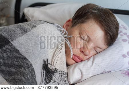 Mature Brunette Woman Sleeping In Bed Under Plaid Blanket, Concept Of Illness Or Cold, Treatment At