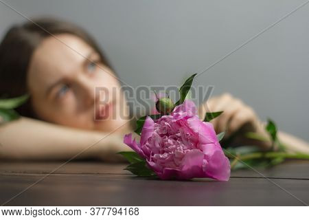 Brunette Girl Florist With Pink Peony On Gray Background, Selective Focus