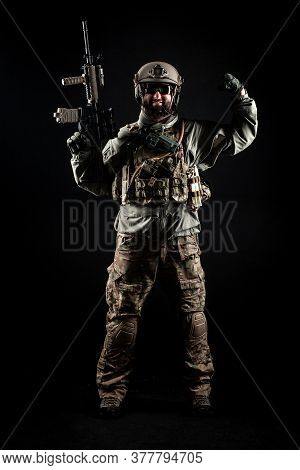 Usa Soldier In A Military Suit With A Rifle Smiles And Shows Strength Against A Dark Background, Ame