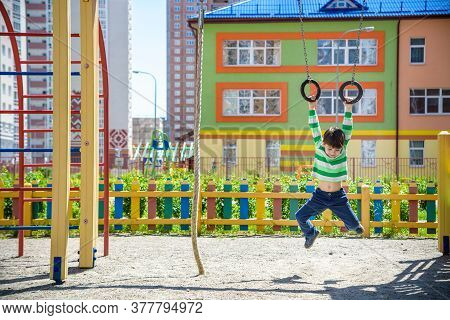 Cute Little Kid Boy Enjoying Climbing Athletic Rings On A Playground. Toddler Child Learning To Clim