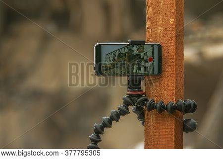 Shooting Time-lapse Video On The Phone With A Tripod Pinned On A Wooden Stick, Demolition Of An Apar