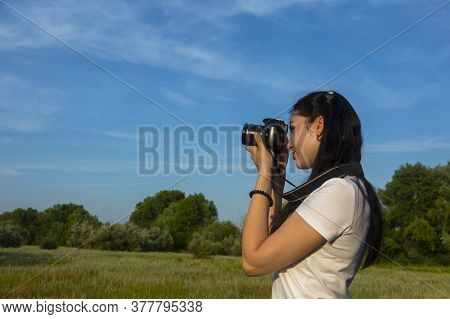 A Beautiful Brunette Photographer Looks Into Her Slr Camera, Shooting Nature With A Digital Camera.
