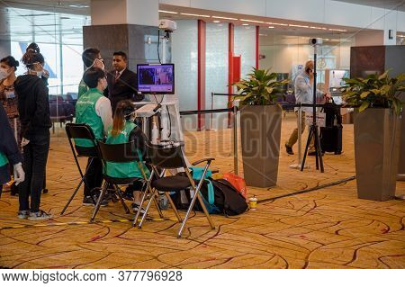Singapore - July 21. 2020: Changi Airport Staff Sit Behind A Thermal Imager At A Temperature Control