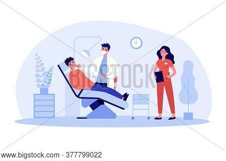 Dentist Examining Patient With Nurse Assistance. Man Visiting Dental Clinic, Sitting In Dentist Chai