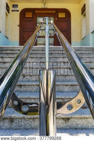 Metal Chrome Railing At Stairs To The Building With Wooden Doors