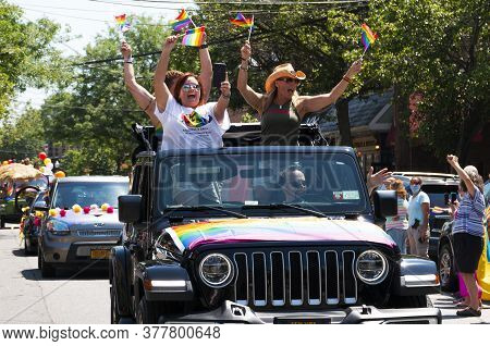 Babylon, New York, Usa - 28 June 2020: Women Waving Gay Pride Flags While Standing Up In A Jeep And