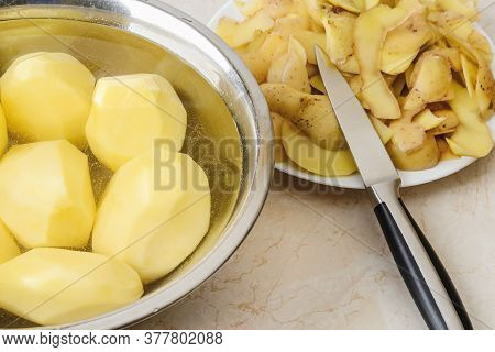 Raw Peeled Potatoes In A Bowl With Water, Potato Peels And A Vegetable Knife On A Plate On The Kitch