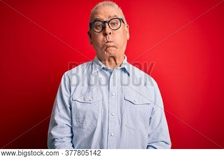 Middle age handsome hoary man wearing casual striped shirt and glasses over red background puffing cheeks with funny face. Mouth inflated with air, crazy expression.