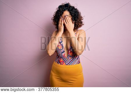Young beautiful arab woman on vacation wearing swimsuit and sunglasses over pink background rubbing eyes for fatigue and headache, sleepy and tired expression. Vision problem