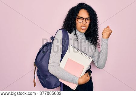 Young african american curly student woman wearing backpack and glasses holding book annoyed and frustrated shouting with anger, crazy and yelling with raised hand, anger concept