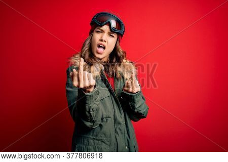 Young blonde girl wearing ski glasses and winter coat for ski weather over red background Showing middle finger doing fuck you bad expression, provocation and rude attitude. Screaming excited