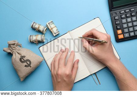 The Concept Of A Diary With Debtors. Hands With A Pen On The Diary Next To A Bag Of Money And A Calc