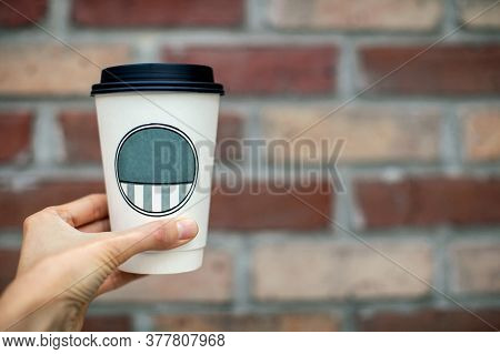Female's Hand Holding A Plastic Cup With A Drink On A Brick Wall Background.