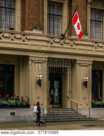 Vancouver, Canada - June 10, 2020: Girl With God Walking On Street In Rainy Day Near Historic Buildi