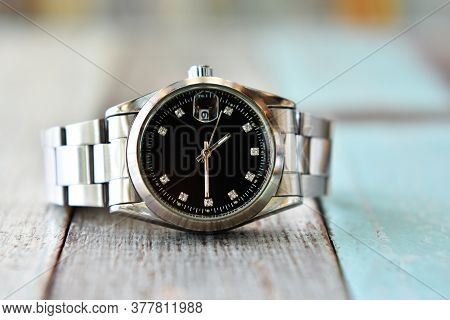 Silver Wristwatch With Black Dial On Table