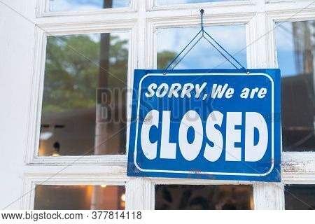 A Sign Board Of Sorry We Are Closed Hang On Door Of  Business.