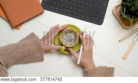 Overhead Shot Of Female Office Worker Hands Holding Coffee Cup On Office Desk With Office Supplies