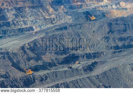 Huge Iron Ore Quarry With Working Dump Trucks And Excavators