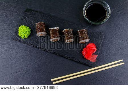 Sushi Maki Rolls With Tuna On Black Slate. Top View
