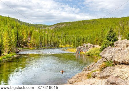 Wyoming, Usa - Aug. 24, 2019: Visitors Swimming And Cooling Off At Firehole River In Yellowstone Nat