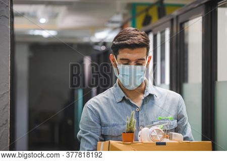 Dismissed Man Worker Wear Face Mask Going From The Office With Holding A Box With His Stuff, Dismiss