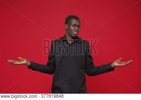 Perplexed Puzzled Young African American Man In Classic Black Shirt Posing Isolated On Red Backgroun