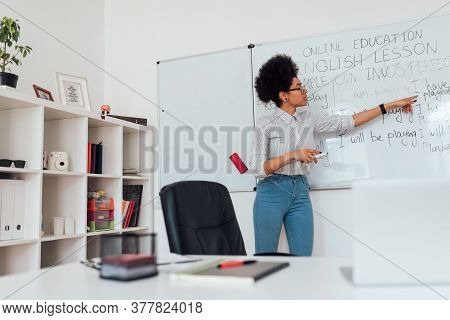 English Tutor. Young Afro American Female Teacher Standing Near Whiteboard And Explaining English Gr