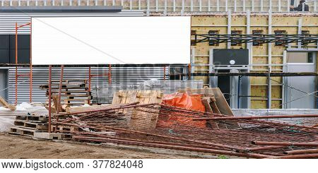 Large Banner Of White Colour Fixed On Building With Different Metal And Wooden Construction Waste On