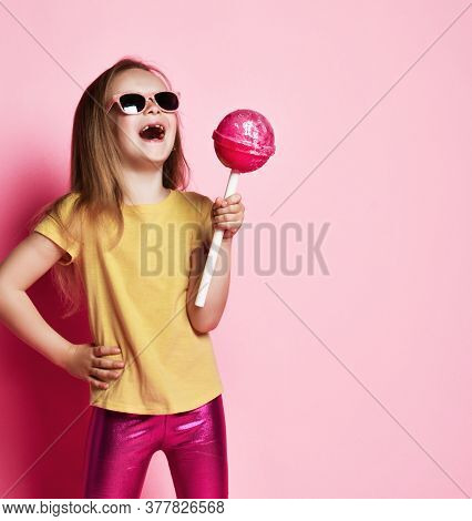 Frolic 6-7 Y.o. Kid Girl In Yellow T-shirt, Shiny Pink Leggings And Sunglasses Holds Big Pink Lollip