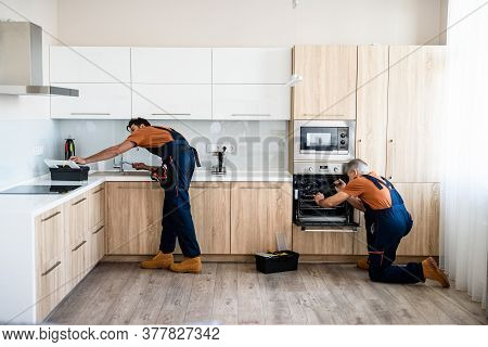 Two Handymen, Workers In Uniform Fixing, Installing Furniture And Equipment In The Kitchen, Using Sc
