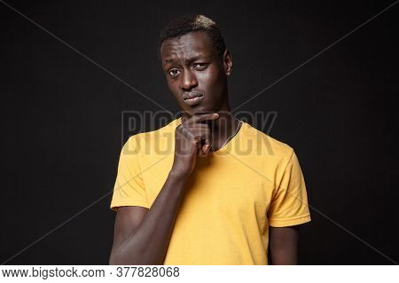 Puzzled Young African American Man Guy In Yellow T-shirt Posing Isolated On Black Background Studio