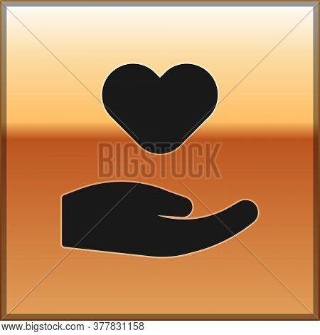 Black Heart In Hand Icon Isolated On Gold Background. Hand Giving Love Symbol. Valentines Day Symbol