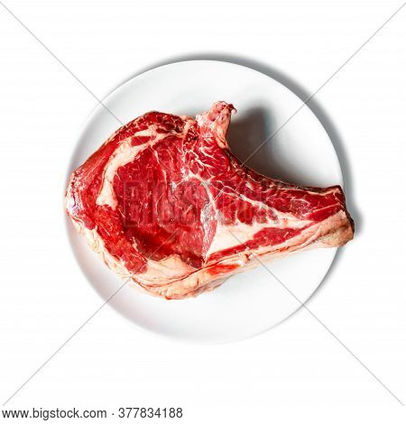Raw Beef Prime Rib On A Plate Isolated On White Background. Top View