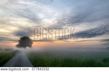 Soft And Dramatic Colorful Sunrise Over A Countryside Farming Area, Creating An Idyllic Scenic Lands