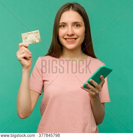 Photo Of Pleased Happy Screaming Young Woman Posing Isolated Over Blue Wall Background Using Mobile