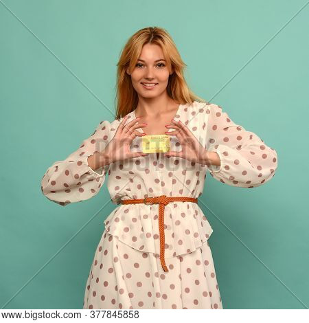 Photo Of Pleased Young Woman Posing Isolated Over Blue Wall Background Holding Debit Or Credit Card.