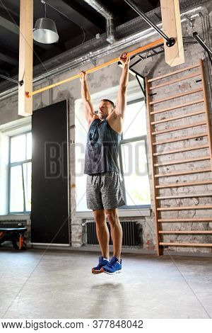 sport, fitness, exercising and people concept - man doing pull-ups on horizontal bar in gym
