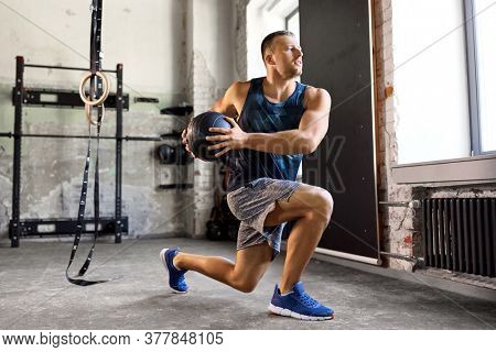 sport, bodybuilding, fitness and people concept - young man exercising with medicine ball in gym