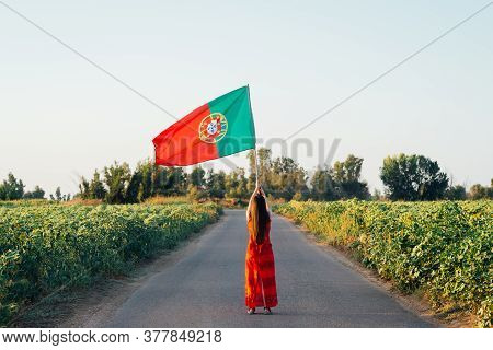 Woman With Portuguese Flag On A Road
