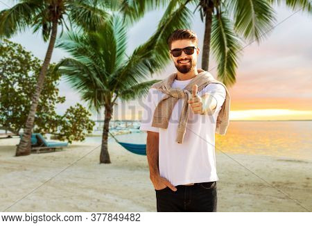 travel, tourism and vacation concept - happy man showing thumbs up over tropical beach background in french polynesia