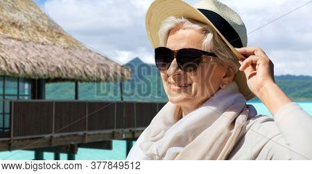 people and leisure concept - portrait of happy senior woman in sunglasses and straw hat over bungalow on tropical beach background in french polynesia
