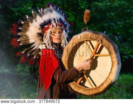 Female Shaman In Native American Indian Clothes And A Headdress Play The Tambourine At Night In The