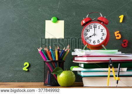 Back To School And Education Concept With Alarm Clock, Green Apple And Stationery Supplies Against B