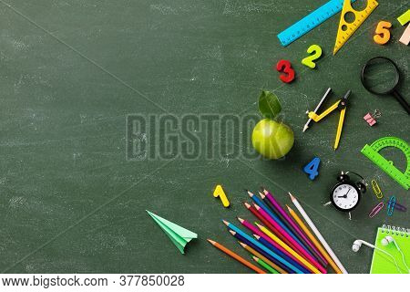 Back To School And Education Concept With Small Alarm Clock, School Supplies And Fresh Green Apple O