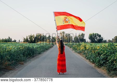 Woman With Spanish Flag On A Road