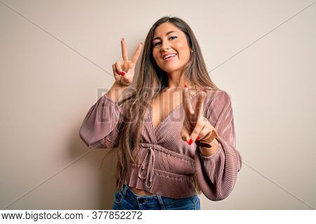 Young beautiful brunette elegant woman with long hair standing over isolated background smiling looking to the camera showing fingers doing victory sign. Number two.