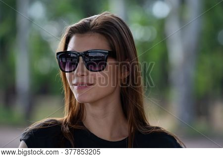 Pretty Girl With Loose Hair In Sunglasses Looks Around, Blurred. Summer Season In The Park.